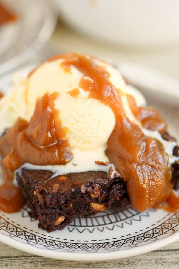 soft brownie on a plate with vanilla ice cream and peanut butter sauce dripped over