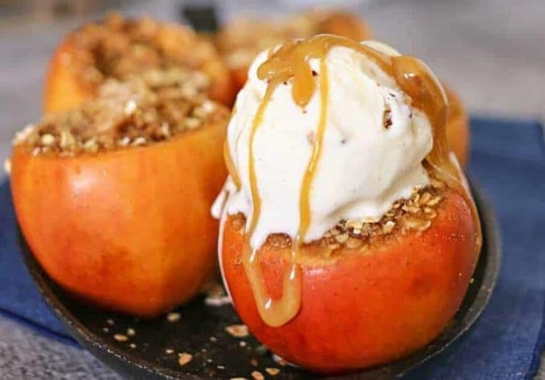 Close up of two apples with crumble on the inside topped with vanilla ice cream drizzles in caramel