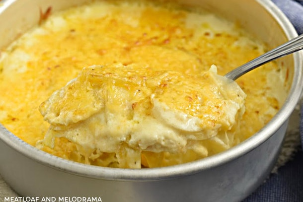 Pot of cheesy, scalloped potatoes being scooped out