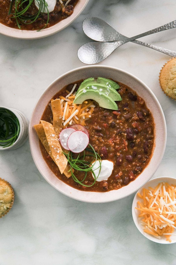 bowl of chili with slices of avocado, radishes, tortilla chips, and sour cream on top