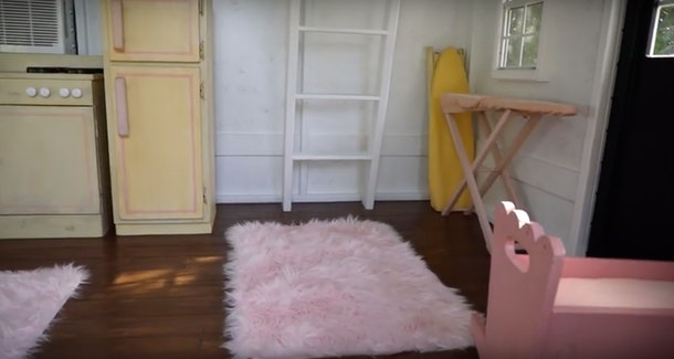 A cot sits in a toy house.
