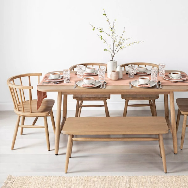 Hearth & Hand with Magnolia dining table, chairs, and bench on grey flooring with white backdrop. The table is set with a pink/coral runner and placements, and dishes at each place.