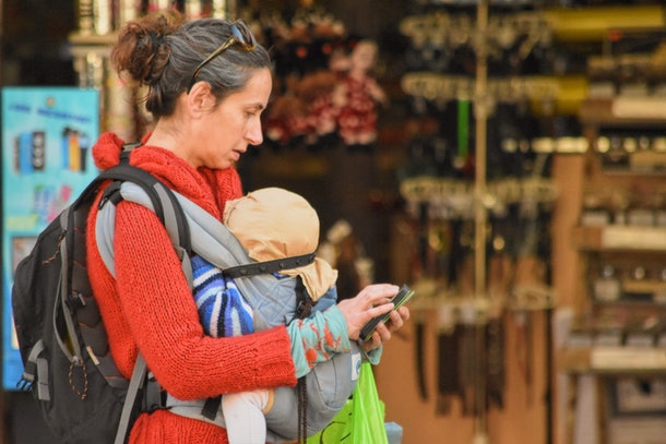 mom checks phone while walking with baby in carrier