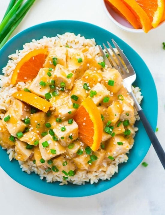 plate of orange chicken on white rice garnished with slices of oranges and diced chives