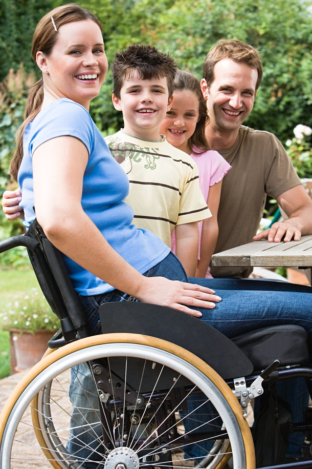 A mom in a wheelchair smiles with her children and partner