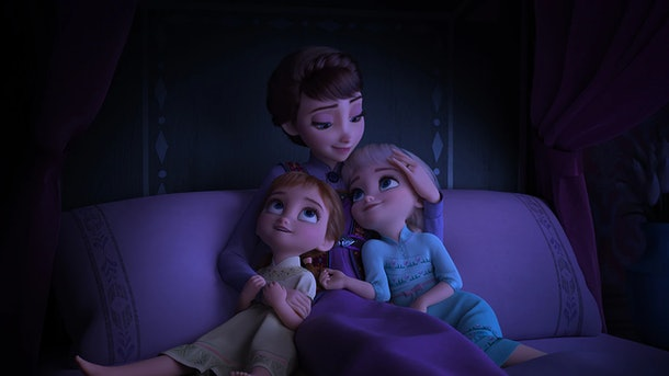 Anna and Elsa snuggle with their mother as children.
