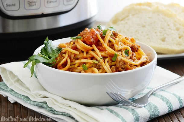 Bowl of spaghetti in red meat sauce garnished in parsley next to a fork with bread in background