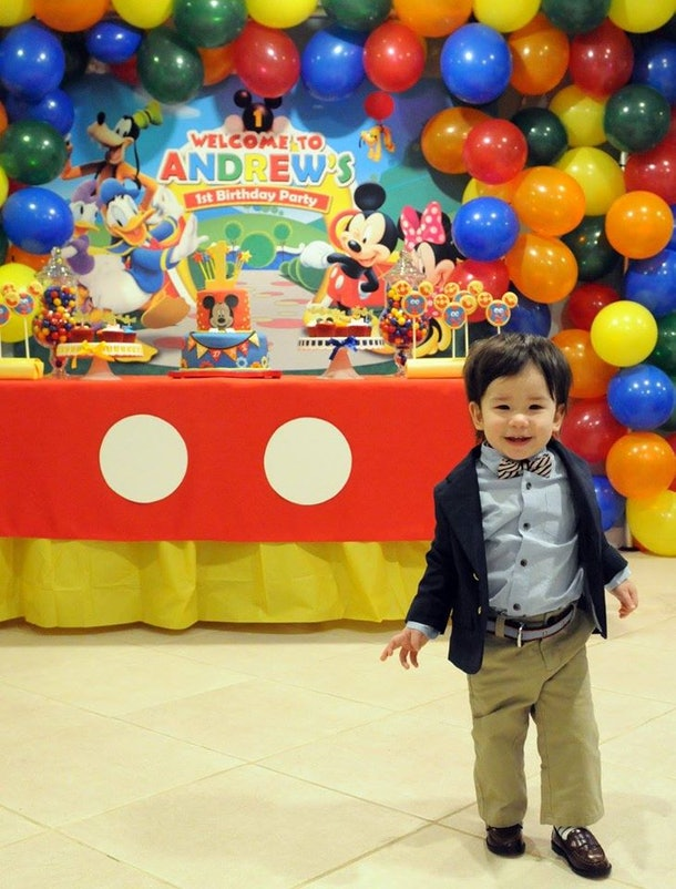 A boy stands in front of his birthday party decorations