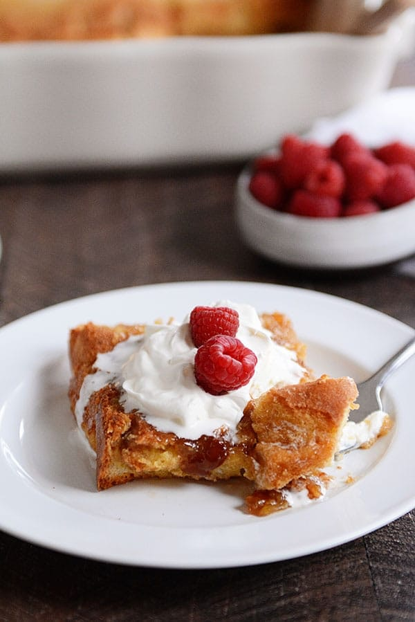 white plate of french toast topped with white cream and raspberries