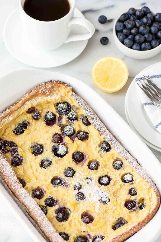 white dish pan with large pancake with blueberries in it sprinkled in powdered sugar.