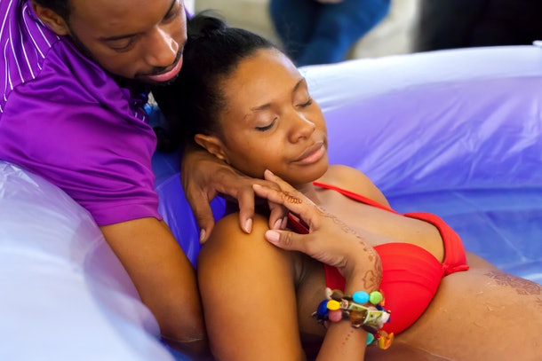 A Black woman in a birthing pool at home, leaning on her partner as she goes through labor and delivery.