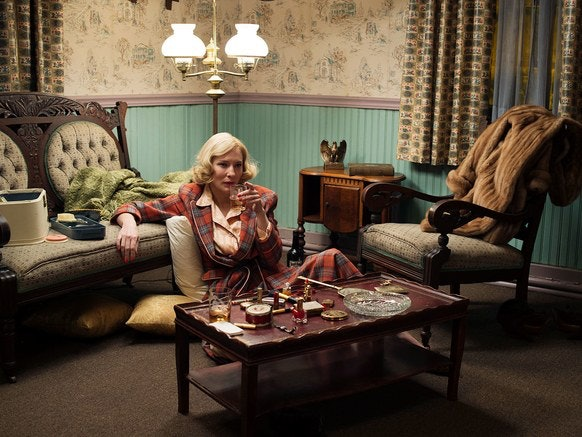 Carol, played by Cate Blanchett, sits on the floor of her living room, drinking a cocktail/