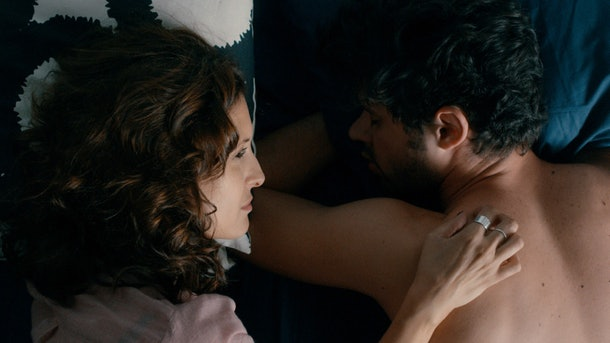 In this still from Dry Martina, a woman and a man are in bed together.
