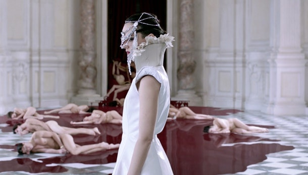 A still from the film Compulsion, in which a woman in white wearing an elaborate headdress stands in from of several naked people who lie in a red puddle on the floor.