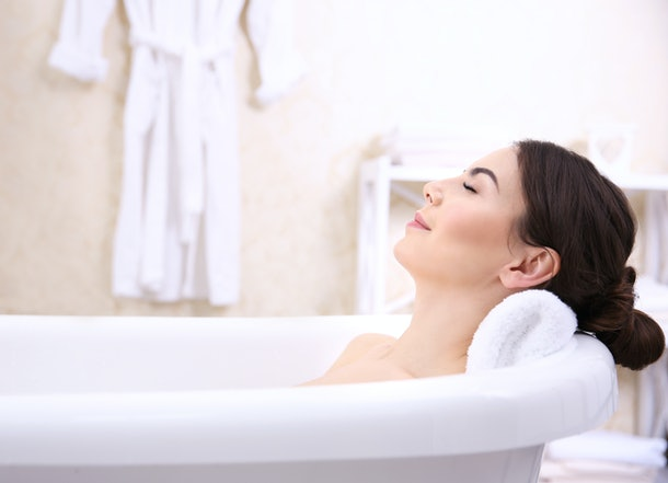 close up of woman's head as she's laying in tub with her eyes closed and neck leaning on edge