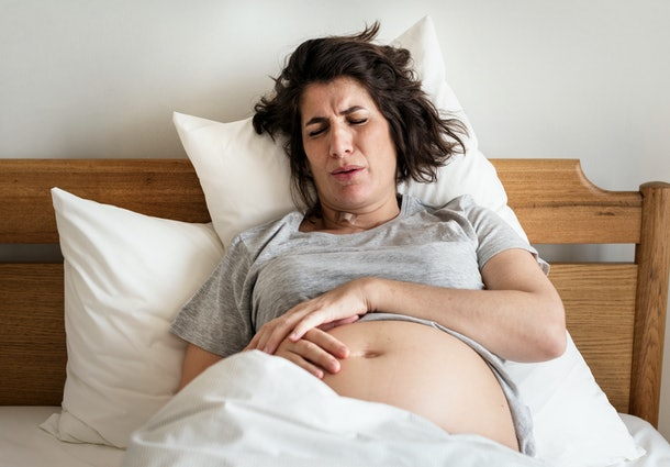 pregnant woman in pain on bed holding belly