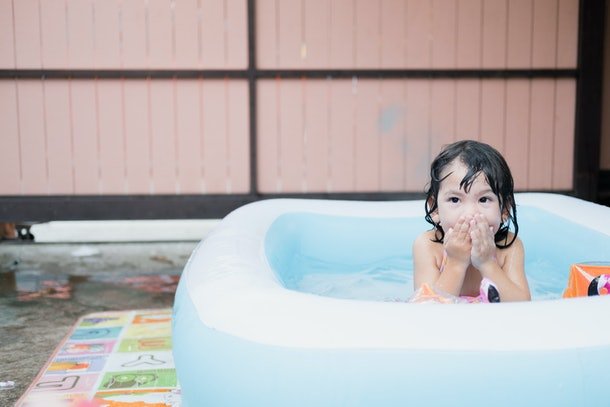 little girl covering mouth in inflatable pool