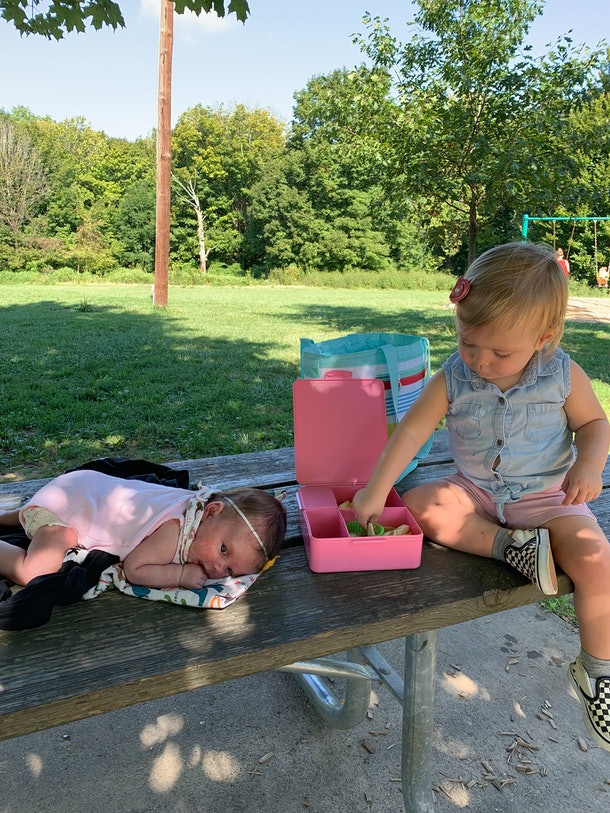 A baby lies on a picnic table next to a toddler