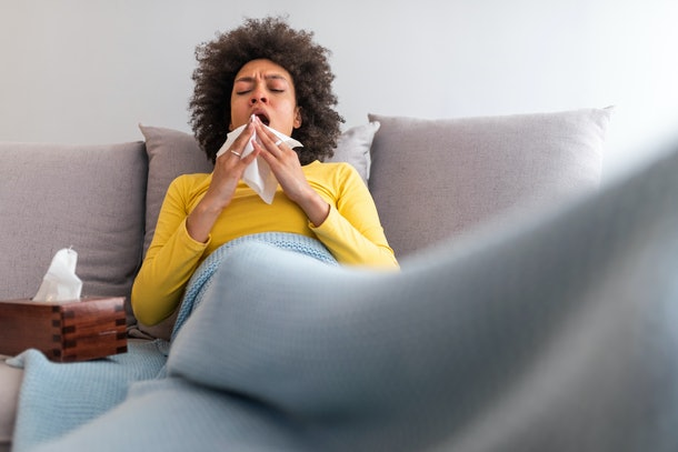 woman coughing into tissue with eyes shut on couch covered in blanket