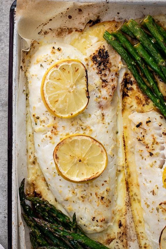 Close up of sheet pan lemon butter fish and asparagus