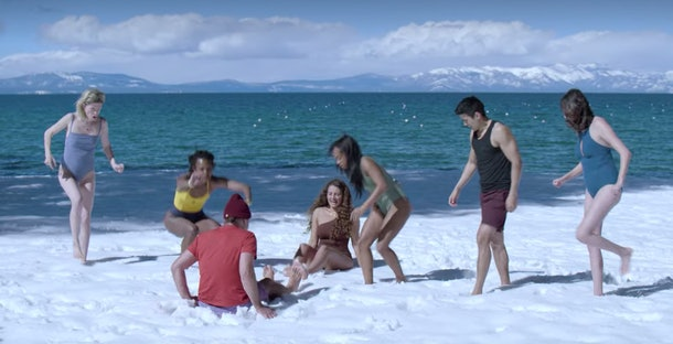 A group of people in swimming suits playing in the snow.
