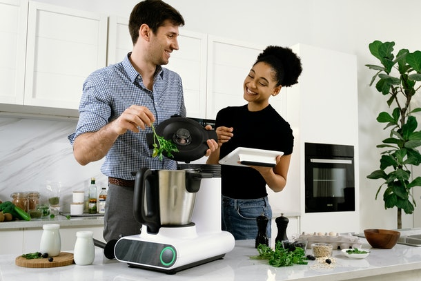 An image of a food processing cooking robot flanked by two humans who are cooking.