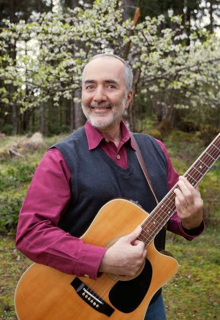 Raffi stands outside with guitar