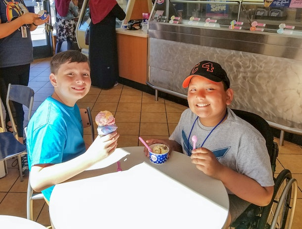A picture of two boys smiling around a table.