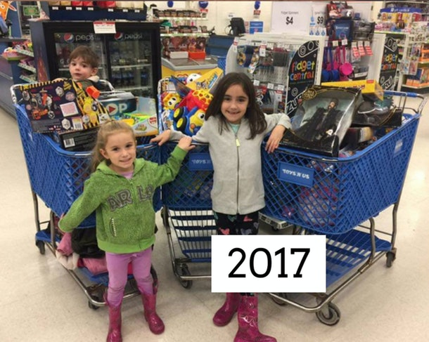 A picture of two girls in front of full carts of toys.
