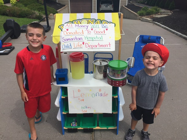 Two boys in front of their lemonade stand.