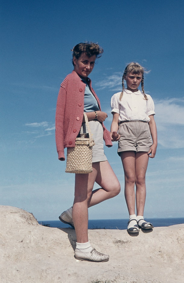 A mother and daughter standing on a beach in a vintage photo