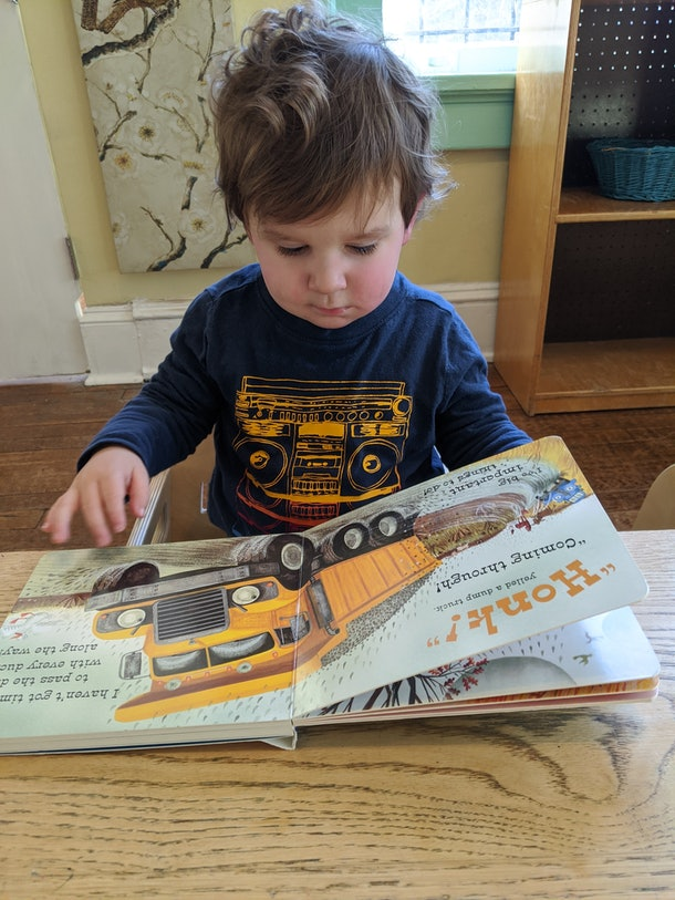 why do books calm my toddler down, toddler reading a book at a table