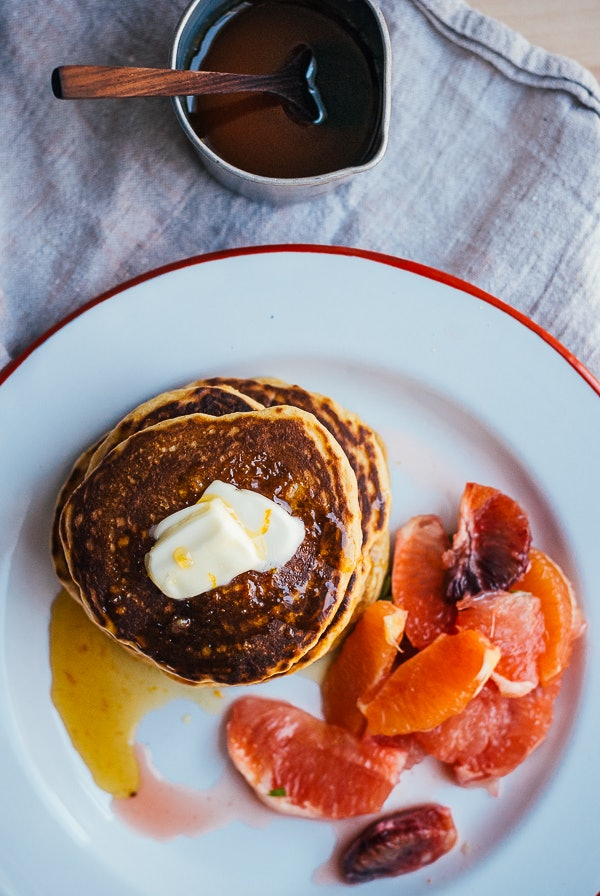 A picture of cornmeal pancakes with orange segments and honey syrup.
