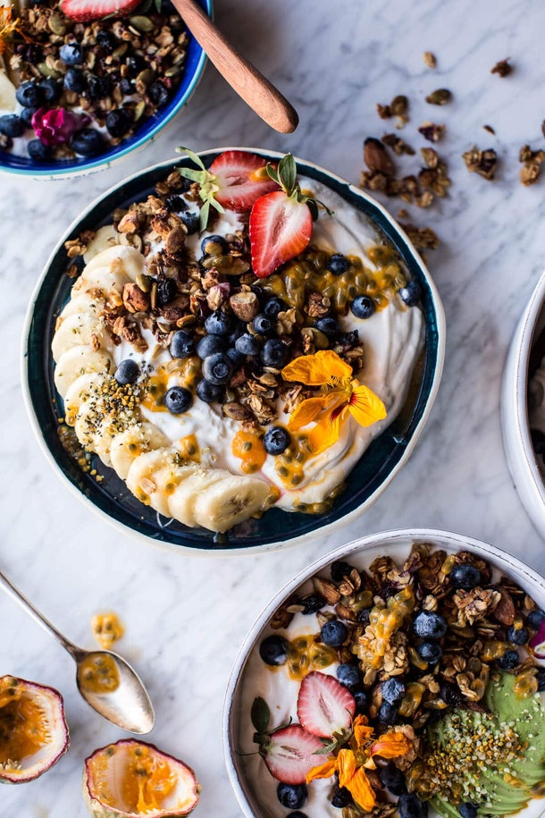 A bowl of granola with yogurt and fruit.