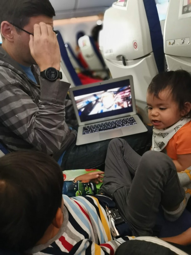 A father and child play on an airplane