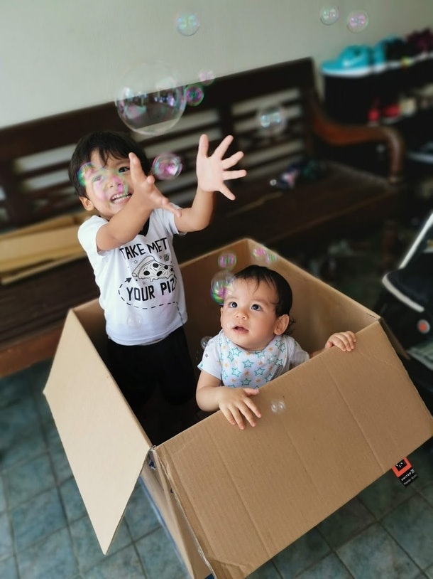 Children catch bubbles inside a cardboard box