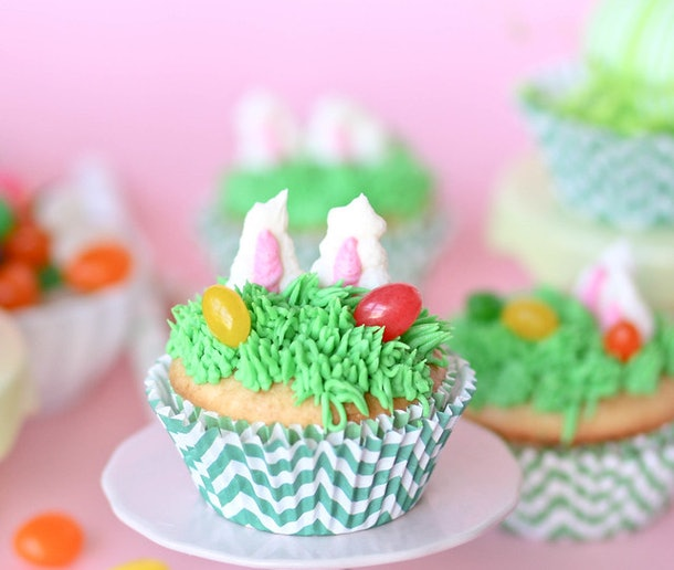 "Cupcake on a plate decorated with icing ""grass"", jelly beans, and bunny ears popping up"