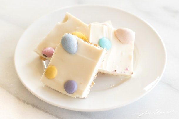 white plate with three pieces of toffee topped with white chocolate and candy eggs