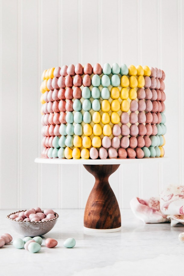 Carrot cake covered in colorful candy eggs in a rainbow swirl pattern on a wooden cake stand with candy eggs scattered around