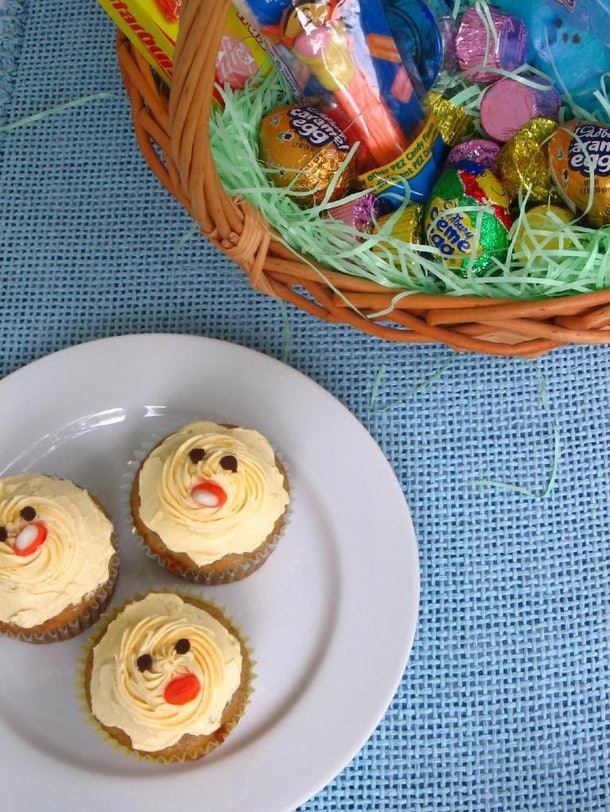 Three cupcakes decorated to look like chicks on a white plate with an Easter basket in the background