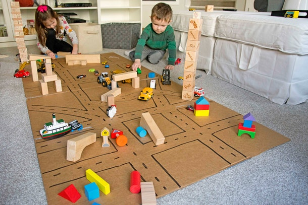 Children play with block cars on a cardboard traffic system.
