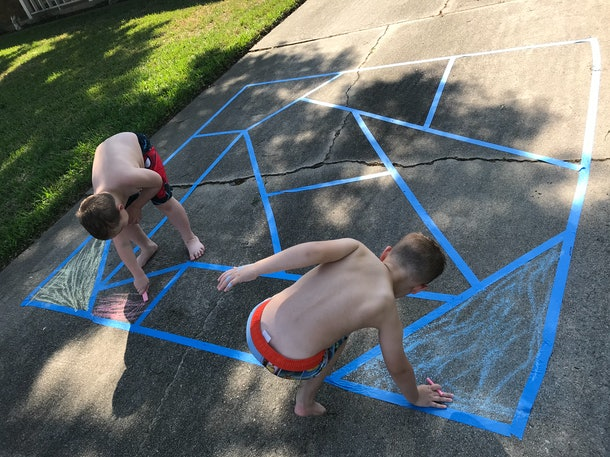 Creating a mosaic with painter's tape is one activity to do with sidewalk chalk.