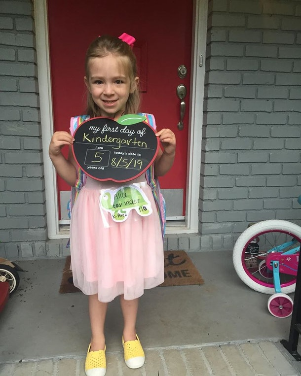 The author's daughter holds a first day of kindergarten photo