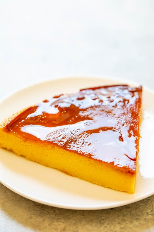 a triangle of caramel flan on a white plate.