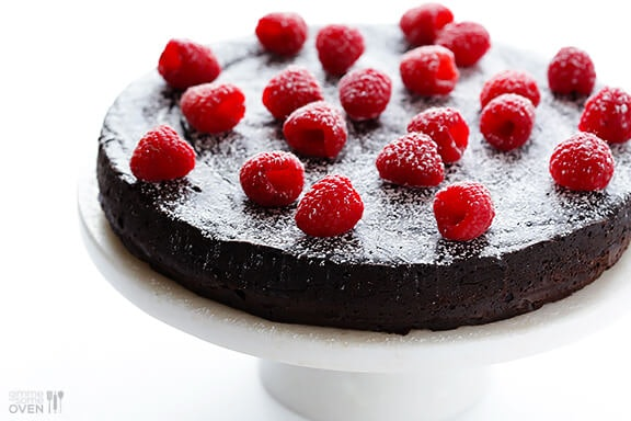 A picture of dark chocolate cake with berries on top.
