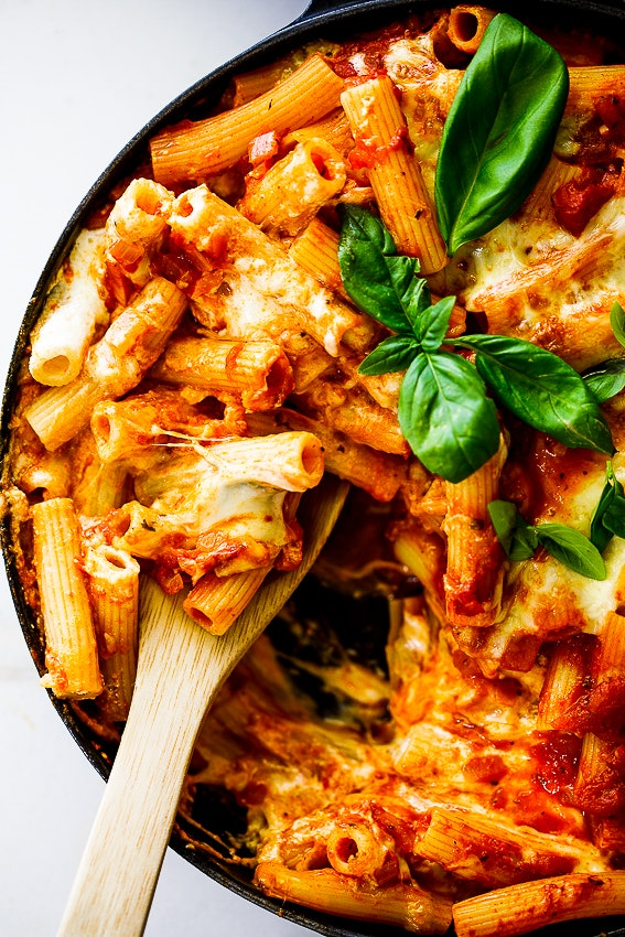 Close up of a dish of baked ziti with garnishes