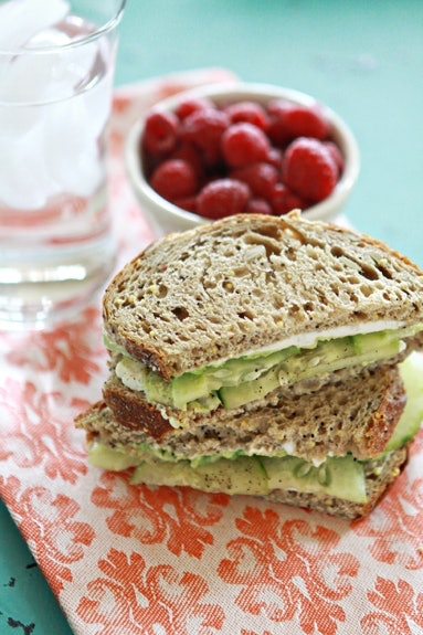 Cucumber Avocado Sandwich on a patterned dish cloth with a bowl of berries and a glass of ice water out of focus