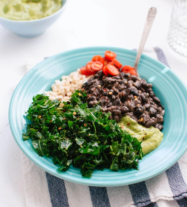 Blue bowl of kale, quinoa, black beans, avocado, and tomatoes sitting on a striped dish towel