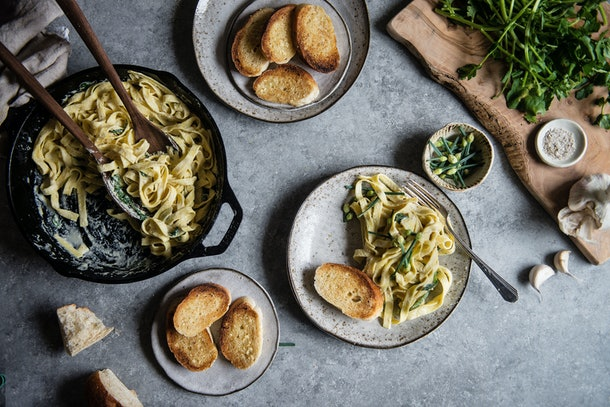 Skillet of chickpea alfredo, plate of garlic bread, plage of a serving of the alfredo and slice of garlic bread all sitting out on a counter top