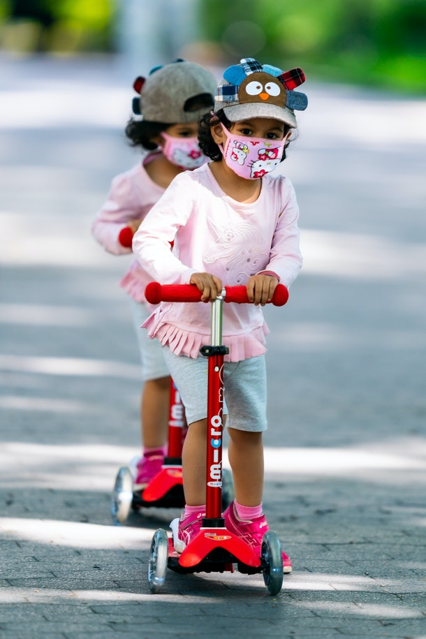 Two girls wear identical protective face masks and outfits on scooters in Washington Square Park during the coronavirus pandemic on May 26, 2020 in New York City. Government guidelines encourage wearing a mask in public with strong social distancing in effect as all 50 states in the USA have begun a gradual process to slowly reopen after weeks of stay-at-home measures to slow the spread of COVID-19.